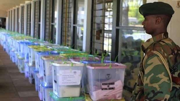 A Kenya Wildlife Service personnel keeps watch Tuesday over unopened ballot boxes at a tallying centre in Nairobi. After the electronic vote system failed, Kenyan officials had to resort to hand-counting ballots.