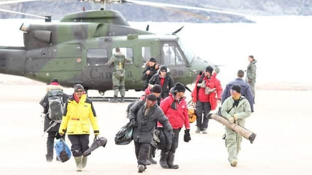 Some of the rescued hunters and tourists walk away from a military helicopter in Arctic Bay, Nunavut.