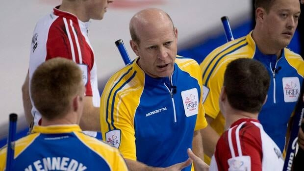 Kevin Martin, centre, shakes hands with Newfoundland and Labrador skip Brad Gushue following the 6-5 win for Alberta on Friday morning.