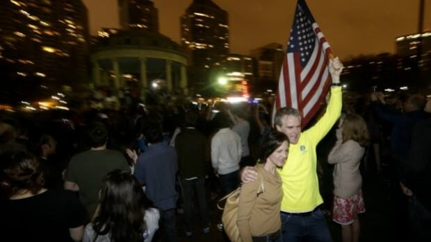 Frank McGillin, right, who has ran three Boston Marathons, and his wife, Peggy, pose for a photograph as a crowd reacts to news of the arrest of one of the Boston Marathon bombing suspects during a celebration at Boston Common Friday.