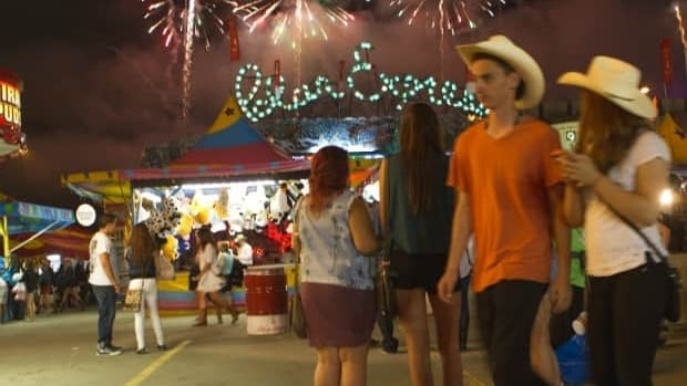 Fireworks explode on the Stampede grounds as people enjoy the midway. From midway rides to the bump in restaurant revenues, the Calgary Stampede brings in more than $127.2 million to Calgary's economy.