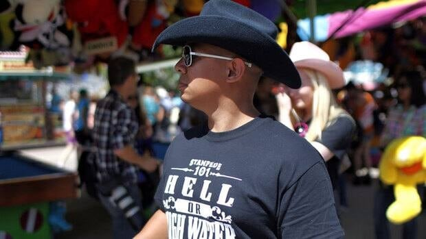 """A man sports a """"Hell or High Water"""" T-shirt as he walks the midway at the Calgary Stampede on Sunday."""
