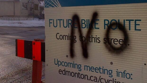 A sign advertising public meetings on Edmonton's bike-lanes plan is defaced.
