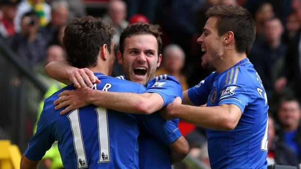 Chelsea's Juan Mata, centre, celebrates with teammates Oscar and Cesar Azpilicueta after scoring the only goal of the match Sunday against Manchester United.
