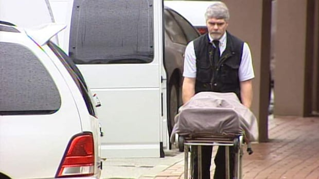 The body of one of the six people who died in the 'Surrey Six' slayings in 2007 is loaded into a coroner's van.