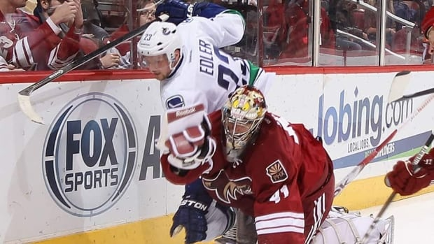 Phoenix Coyotes goaltender Mike Smith, left, is hit by Vancouver Canucks defenceman Alex Edler on Thursday night.