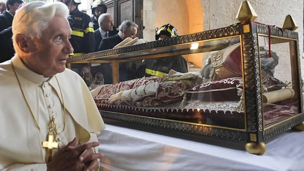 Pope Benedict XVI stands by the salvaged remains of Pope Celestine V, in the 13th-century Santa Maria di Collemaggio Basilica, the symbol of the city of L'Aquila, in April 2009