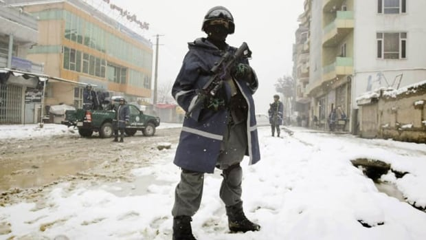 A suicide bomber carrying an umbrella as a shelter against heavy snow crossed a street in the Afghan capital Kabul Wednesday morning and exploded, engulfing the undercarriage of the bus in flames.