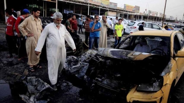 Iraqis gather at the scene of a car bomb attack at a used cars dealers parking lot in Habibiya neighborhood of eastern Baghdad, Iraq. A wave of car bombings tore through mostly Shia Muslim neighbourhoods of the Baghdad area, killing and wounding dozens of people.