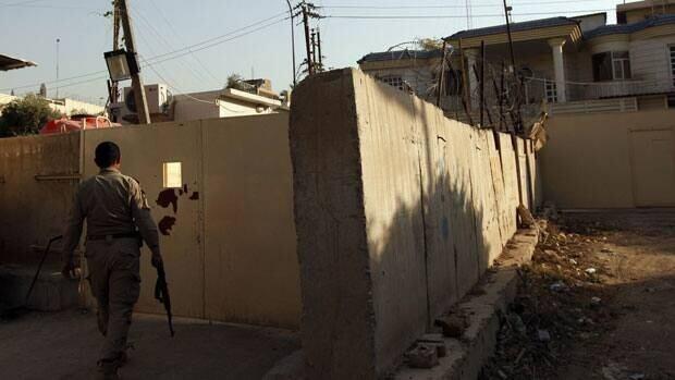 A security guard walks outside the Al Jazeera building in Baghdad April 28, 2013.