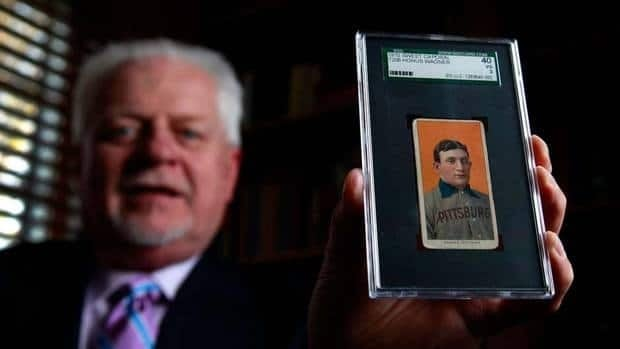 Bill Goodwin holds a 1909 Honus Wagner baseball card back in March of last year that sold for $1.2 million. A similar card went for $2.1 this week.