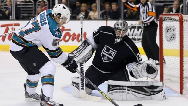 Tommy Wingels of the San Jose Sharks, left, and goaltender Jonathan Quick of the Los Angeles Kings during Game 2 on May 16, 2013 in Los Angeles, California.