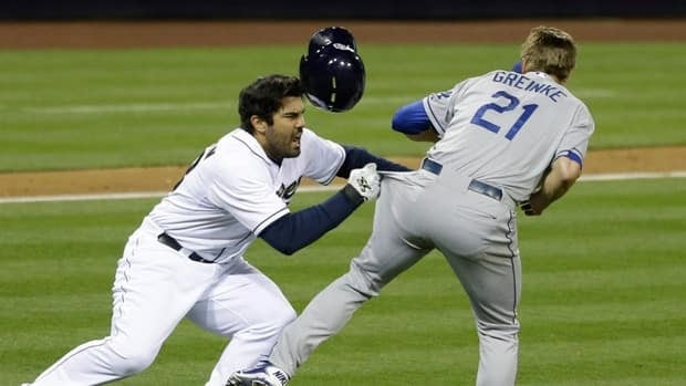 San Diego Padres' Carlos Quentin charges into Los Angeles Dodgers pitcher Zack Greinke after being hit by a pitch in the sixth inning of baseball game in San Diego, Thursday, April 11, 2013.