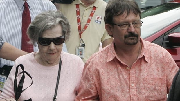 Powerball winner Gloria C. Mackenzie, 84, left, leaves the lottery office escorted by her son, Scott Mackenzie, after claiming a single lump-sum payment of about $370.9 million US before taxes on Wednesday in Tallahassee, Fla.