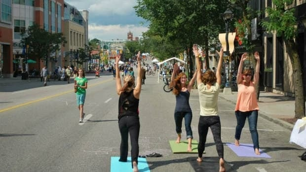 Women do yoga in the middle of King Street in UpTown Waterloo during the 2012 Open Streets festival. The festival has been criticized by some local stores who say shutting down streets in the city core is bad for business.