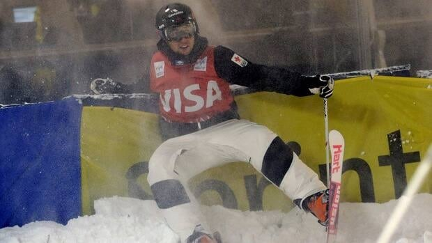 Alex Bilodeau, of Canada, slams in to the barricade after crossing the finish line at the men's dual moguls on Saturday in Park City, Utah. Bilodeau came in first place.