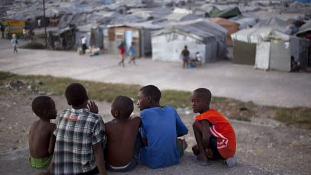 A group of boys sit on the rooftop of a home damaged by the 2010 earthquake, across from the Jean Marie Vincent camp where they now reside, in Port-au-Prince, Haiti, Jan. 9. Saturday marks the third anniversary of the devastating 7.0 magnitude earthquake. There are 358,000 people still living in the encampments that sprouted throughout the city after the earthquake.