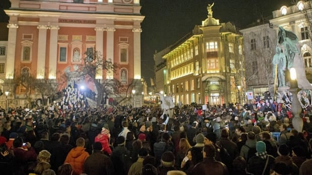 About 10,000 protesters rally outside the Slovenian parliament on Friday to demand the resignation of Prime Minister Janez Jansa and opposition leader Zoran Jankovic in the wake of corruption allegations.