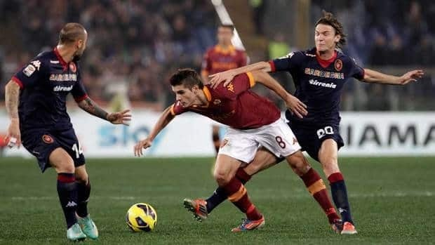 AS Roma forward Erik Lamela, of Argentina, centre, is challenged by Cagliari defender Francesco Pisano, left, and midfielder Albin Ekdal during their match on Friday.