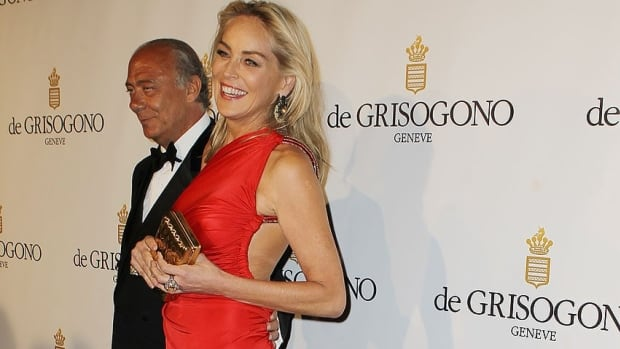 Actress Sharon Stone poses with Fawaz Gruosi, director of jewelry company de Grisogono, at its 20th anniversary party at the Eden Roc hotel in Antibes, near Cannes on Tuesday. Thieves got past a bevy of stars and more than 80 security guards at the event to steal a necklace worth $ 2.7 million Cdn.