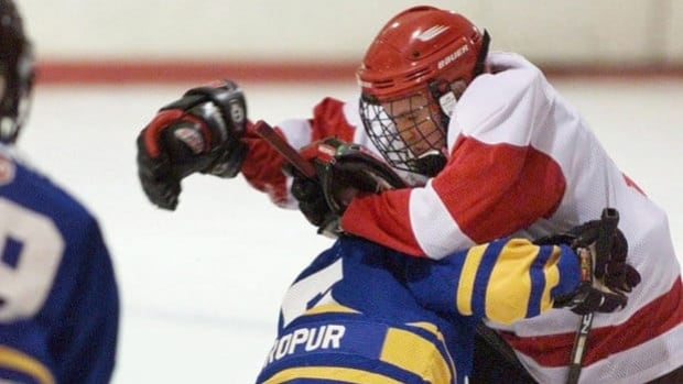 A player from the Dartmouth Whalers collides with a member of the Cole Harbour Red Wings, right, in peewee A action in Halifax on Feb. 15, 2001. Hockey Nova Scotia announced it will ban bodychecking for peewee players as momentum grows to have the disputed practice eliminated for adolescents who doctors say are suffering high rates of hockey-related concussions and fractures.