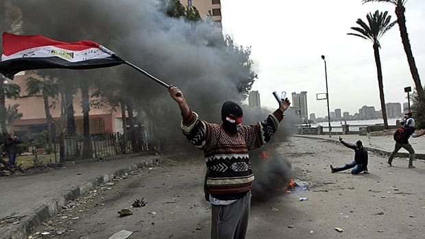 A protestor, ostensibly part of the Black Bloc, waves the Egyptian flag while clashing with riot police near Cairo's iconic Tahrir Square on Monday.