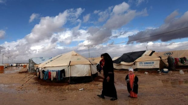 A Syrian refugee woman walks with her two kids at Zaatari Syrian refugee camp, near the Syrian border in Mafraq, Jordan, Wednesday, Jan. 9, 2013. Jordanian officials report an increase in Syrians coming across the border in recent days as clashes continue in Syria.