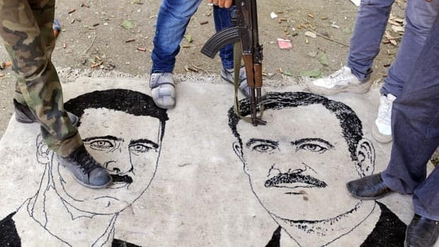 Syrian opposition fighters stand on a mat with drawings of President Bashar al-Assad, left, and his late father Hafez in the northern town of Ras al-Ain in November.