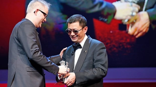 Denis Côté, left, receives the Silver Bear Alfred Bauer prize for his film Vic + Flo Saw a Bear from Jury Chair Wong Kar Wai during the awards ceremony in Berlin Saturday night.