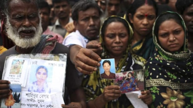 People hold out pictures of missing relatives in Savar, near Dhaka, Bangladesh. Rescue workers in Bangladesh have now given up hope of finding any more survivors in the remains of the factory building that collapsed on April 24.