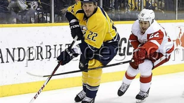 Detroit Red Wings right wing Jordin Tootoo, right, tries to slow down Nashville Predators defenceman Scott Hannan during the first period of an NHL hockey game Tuesday.