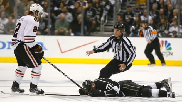Linesman Brad Kovachik, right, moves in to restrain Chicago Blackhawks' Duncan Keith, left, after he hit Los Angeles Kings' Jeff Carter in the face (77) with his stick during the second period of Game 3 on Tuesday.