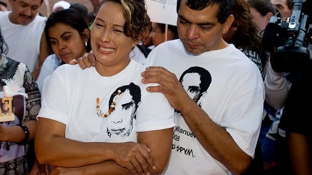 Gilberto and Lilian Villanueva, parents of Fredy Villanueva, attend a vigil at at the site where their son was killed on the first anniversary of his death in Montreal, Sunday, Aug. 9, 2009.