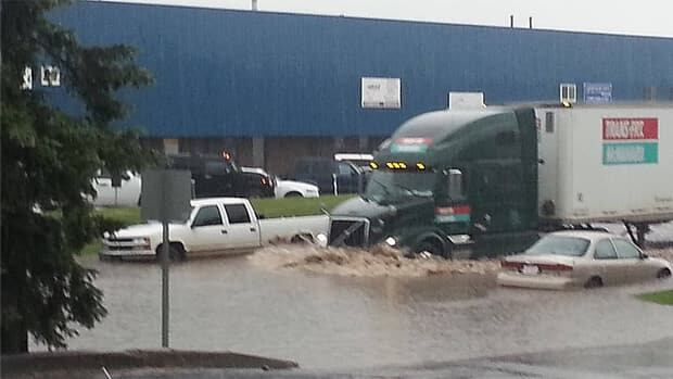 Traffic plows through water in east Edmonton at 45th Street and 82 Avenue during the noon hour Monday.