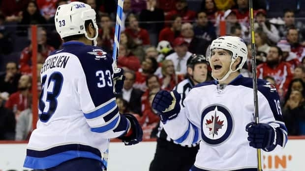 Winnipeg Jets defenceman Dustin Byfuglien celebrates with center Jim Slater after Slater's goal in the second period. Alex Brandon/Associated Press