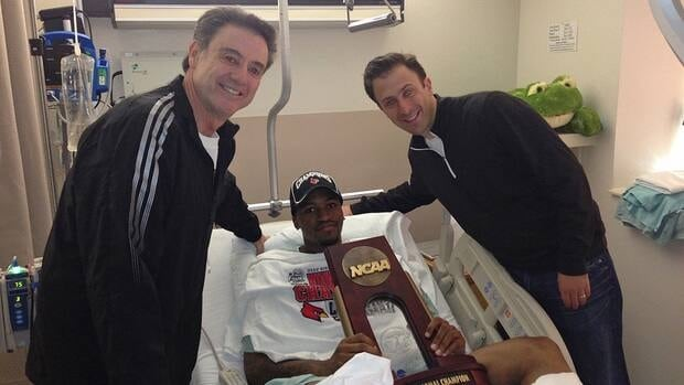 In this photo released by the University of Louisville, injured Louisville guard Kevin Ware lies in a hospital bed holding the NCAA Regional Championship trophy flanked by coach Rick Pitino, left, and former Louisville assistant coach Richard Pitino on Monday.