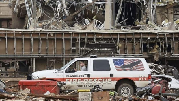 A fire official drives through the rubble of Moore Medical Center after a tornado struck Moore, Oklahoma, on Monday.