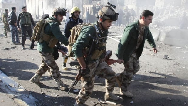 A wounded person is carried by soldiers at the site of a suicide bomb attack in Kirkuk, 250 km north of Baghdad. A separate attack also hit the town of Taji, killing 18.