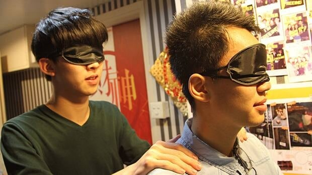 Tom Wong, left, and Barry Lee are about to be led blindfolded into the Prison Break room at Freeing Hong Kong, a popular new entertainment venue where players are locked in a room and have to solve puzzles to get out.