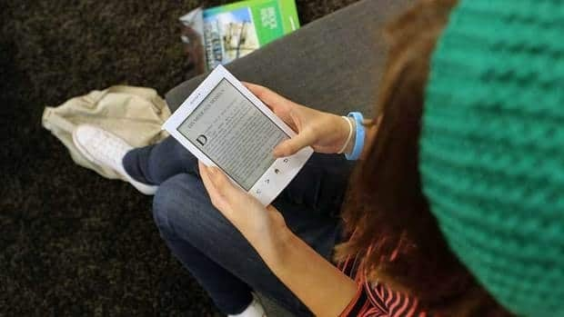 A young girl reads an e-book at the Frankfurt Book Fair. Children are reading more on electronic readers.