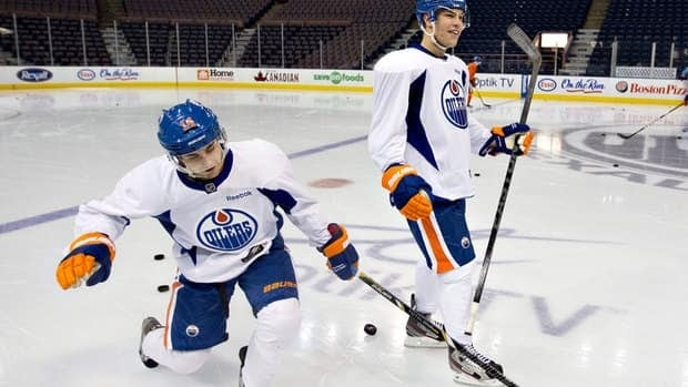 Edmonton Oilers Jordan Eberle, left, shows off his celebration move to teamate Taylor Hall during training camp Monday.