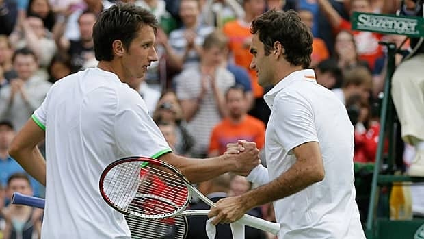 Sergiy Stakhovsky of Ukraine, left, shakes hands with Roger Federer of Switzerland after he stunned the seven-time champ Wednesday.