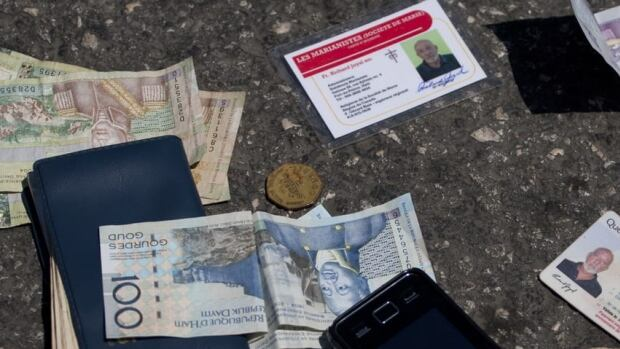 Identification cards, cash, a phone, a key and an item with a bank logo lie on the street after being placed there by authorities next to the body of Canadian missionary Richard E. Joyal, after he was killed Thursday in Haiti.