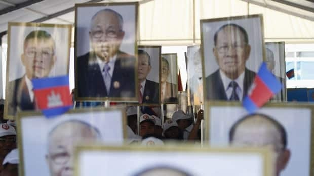 Supporters of the Cambodian People's Party (CPP) hold portraits of their party leaders as they attend an election campaign in Phnom Penh June 27, 2013.