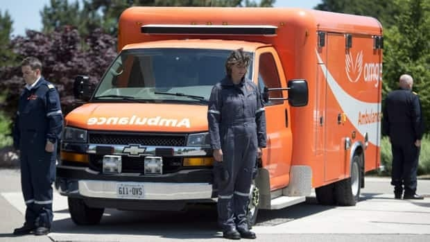 Ornge employees pause outside a memorial service for the two pilots and two paramedics who died late last month in an air ambulance crash, in Toronto, Tuesday, June 18, 2013.
