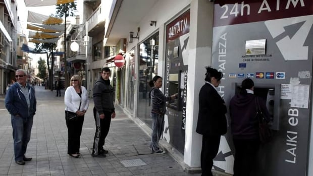 People wait to use the ATM machines outside a closed Laiki Bank branch in capital Nicosia, Cyprus. Cypriot officials rushed Wednesday to find new ways to stave off financial ruin, including asking Russia for help, after Parliament rejected a plan to contribute to the nation's bailout package by seizing people's bank savings.