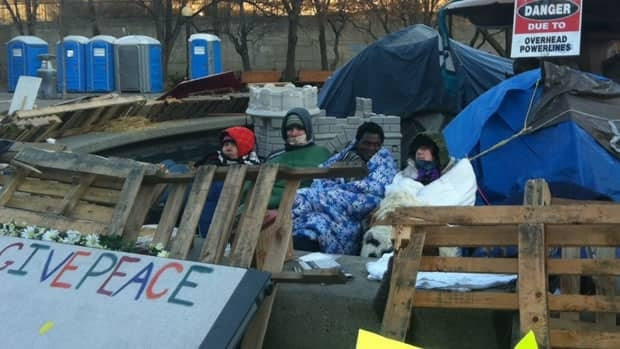 Four Occupy Ottawa holdovers huddle in the cold on Tuesday. The protesters were evicted in November 2011.