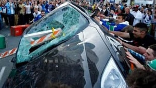 Aman Singh Aujla, in the black T-shirt, was sentenced for smashing a police car and the windows of pizza shop during the Stanley Cup riot of June 2011.