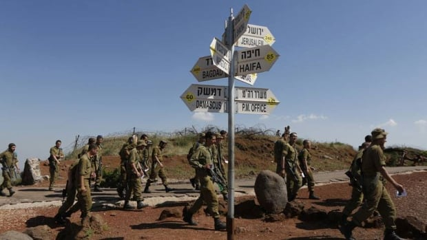 Israeli soldiers walk past signs pointing out distances to different cities at an observation point on Mount Bental in the Israeli-occupied Golan Heights on May 5, 2013.