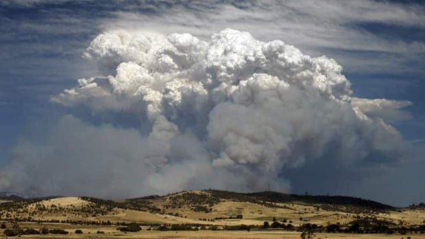 Smoke from a bushfire billows over hills on Australia's island state of Tasmania on Friday. The fires have razed 20,000 hectares of forests and farmland.